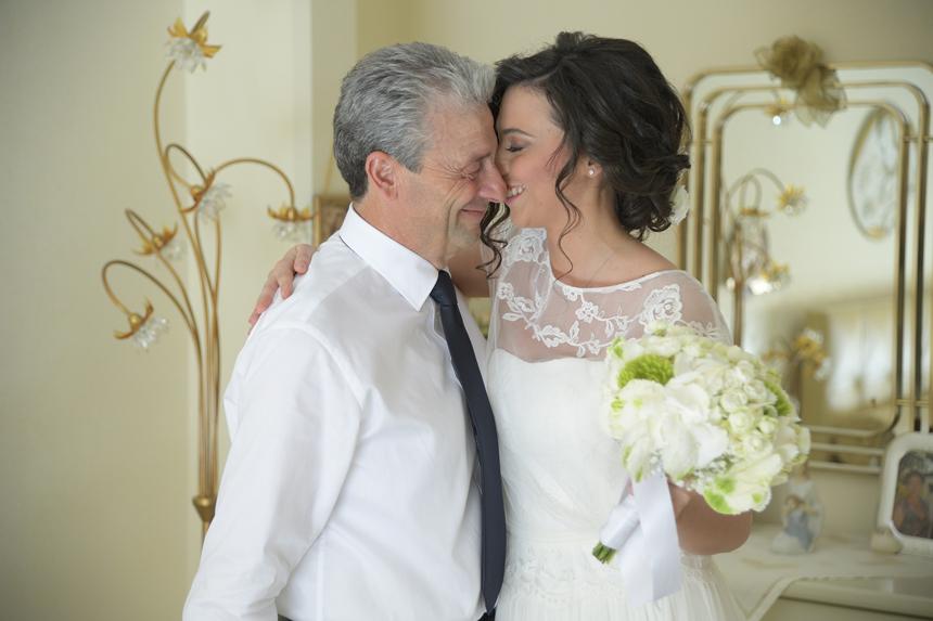 la sposa abbraccia il padre con bouquet