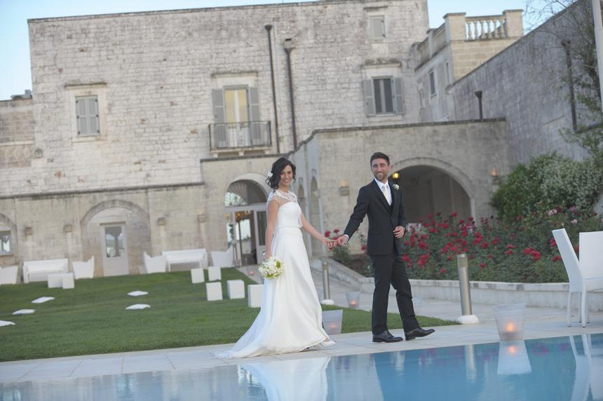 sposi che passeggiano a bordo piscina, foto matrimonio al tramonto