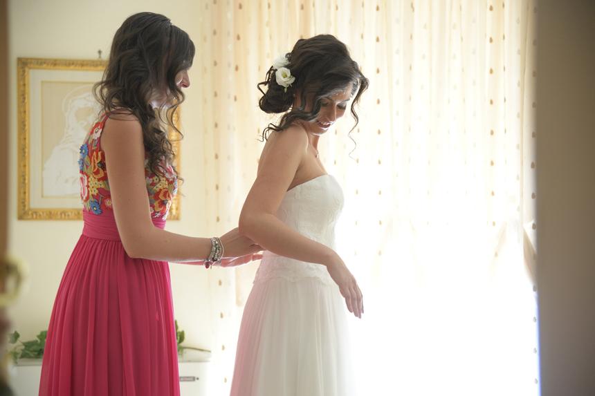 la sposa si veste con l'aiuto della sorella, matrimonio total white