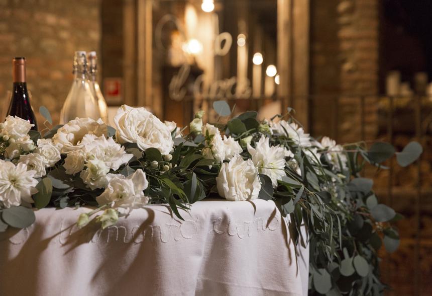 tavolo degli sposi con runner floreale di rose bianche